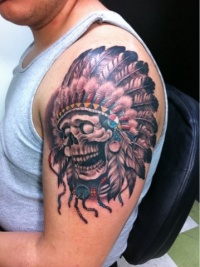 Coloured skull in indian headdress tattoo on shoulder